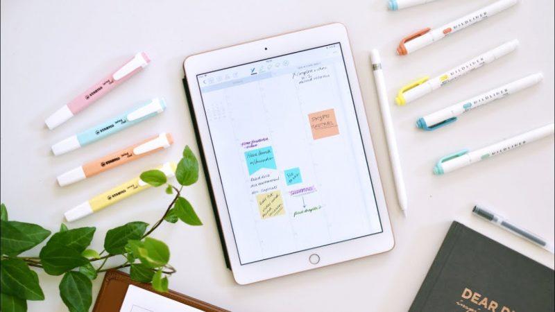 tablet em cima de uma mesa com várias canetas marca textos de cores diferentes em volta