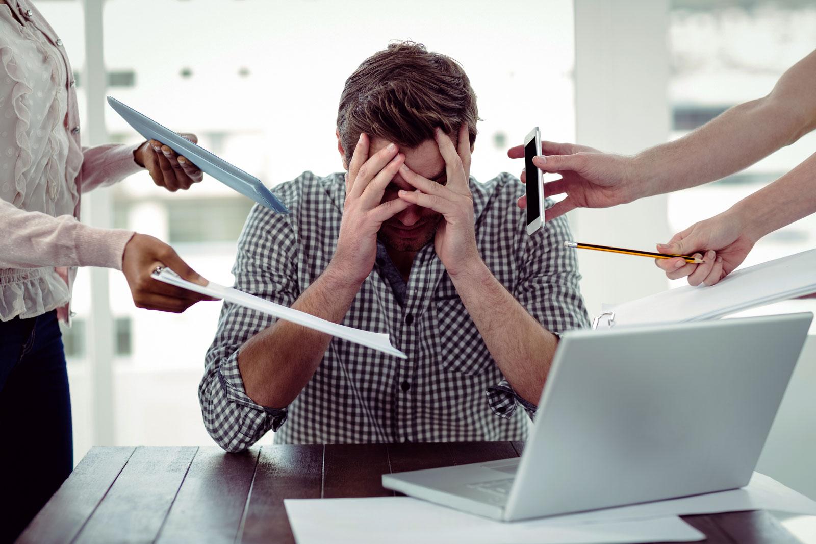homem sentado a uma mesa com um notebook. Ele está com a mão na cabeça mostrando estresse por ter muitas tarefas a realizar
